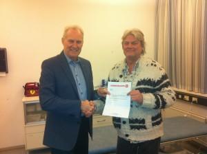 Johanniterhjælpens næstformand, Ulrik greve af Rosenborg, overrækker beløb på 10.000 kr. til Michael Esbensen, leder af Morgencafeen for Hjemløse i København.
